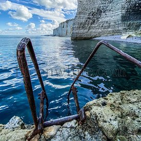 Ladder going down in the sea with on the background Limestone cliffs at Etretat, French Coast