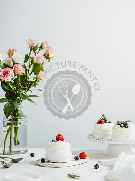 Mini Pavlova cakes with fresh berries, copy space, vertical