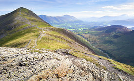 The rugged path from the summit of Hobcarton with Grisedale Pike in the distance and the valley of Coledale Beck far below, t...