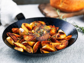 Roasted potato wedges with rosemary in a wrought iron pan on a tablecloth