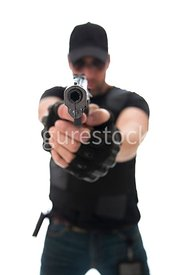 A Figurestock image of a blurred man pointing a gun – shot from eye level.