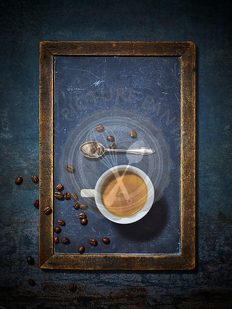 An espresso coffee in a blue ceramic cup against a chalk and blue background. in a blue ceramic cup and saucer against a chal...