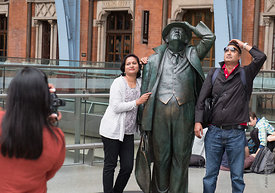 #121376  Tourists imitating, 'Sir John Betjeman' statue by Martin Jennings at St Pancras International railway station, Londo...