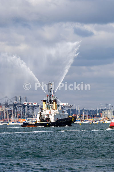 Tug boat spraying water whilst underway