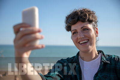 A YOUNG GEN Z LESBIAN LOOKING AT HER PHONE AND TAKING SELFIES. SHE IS SMILING AND PULLING FUNNY FACES