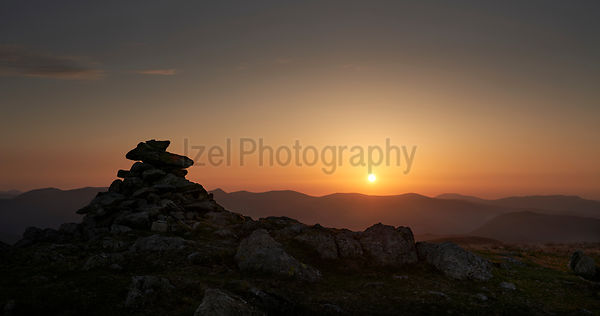 The warm evening sunlight of the mountain summit cairn of Rampsgill Head at sunset in the Lake District UK.