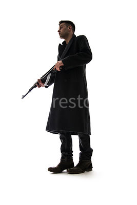 A semi-silhouette of a mystery man in a long black winter coat, holding an AK-47– shot from low level.