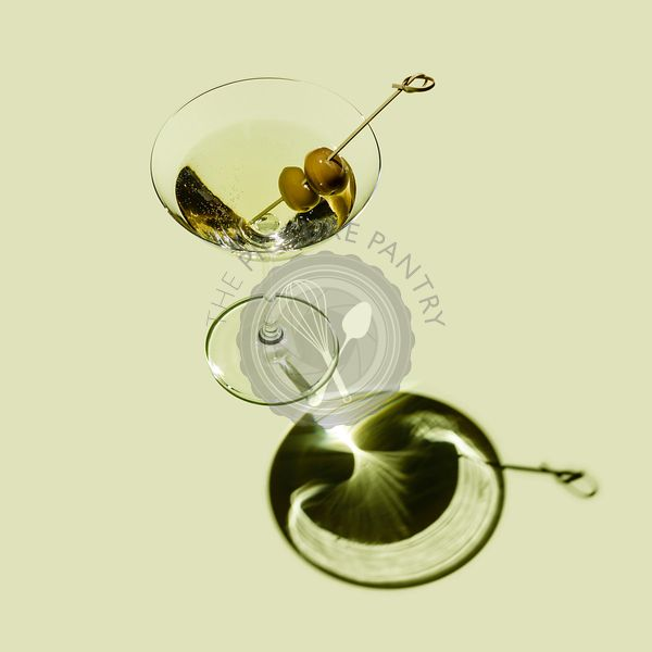Classic Martini Cocktail with green olives on green background
