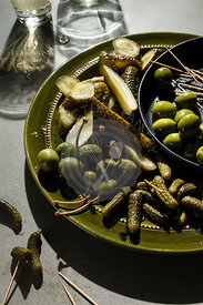 A selection of pickled gherkins, caper berries and green olives on an olive green plate. Shadows on the concrete background s...