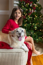 Happy dog and smiling young girl in front of Christmas Tree