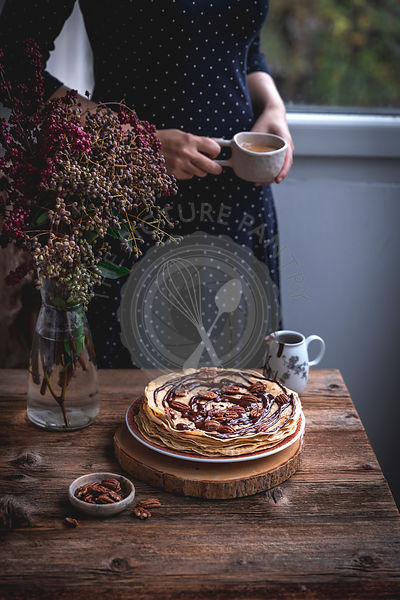 Stack of crepes with melted dark chocolate and pecans, woman in the background drinking coffee