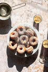 Fried doughnuts coated with icing sugar and two glasses of coffee on the table