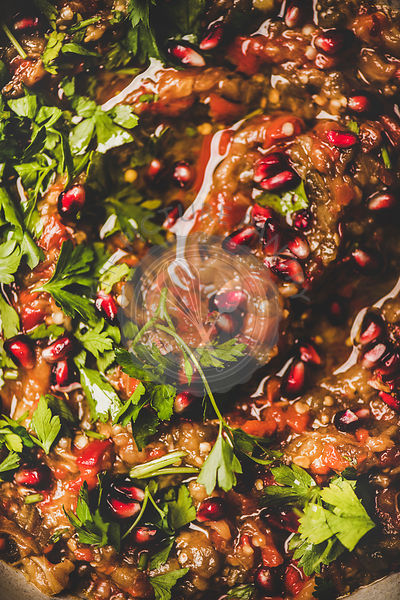 Babaganoush cold dip seasoned with parsley and pomegranate seeds, close-up