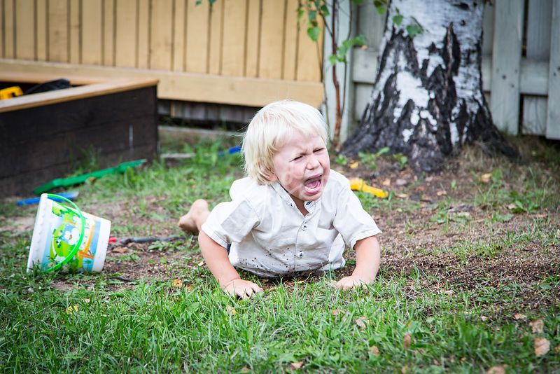 Pieni poika itkee kaaduttuaan juoksuleikissä|||Small boy cries out after falling down in the middle of the running play