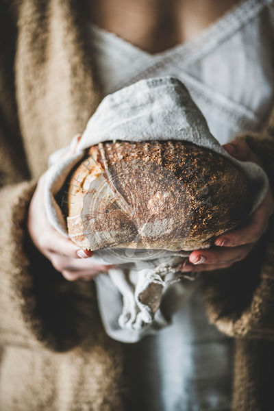 Woman holding healthy rye Swedish bread round loaf in hands