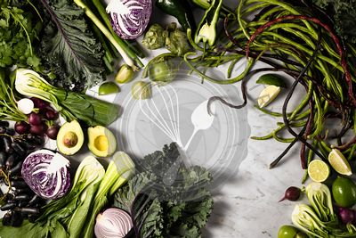 A variety of green and purple produce laid out on a marble background.