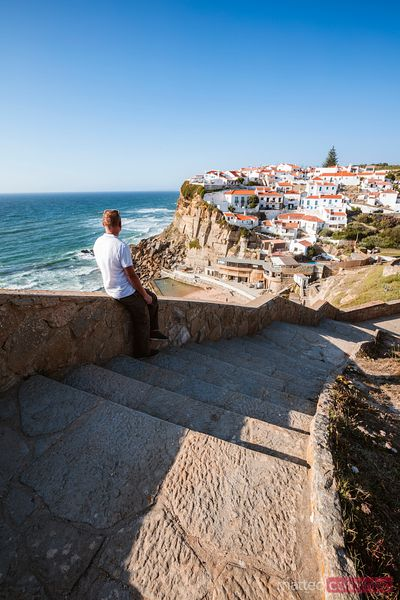 Man looking at town perched on cliff, Portugal