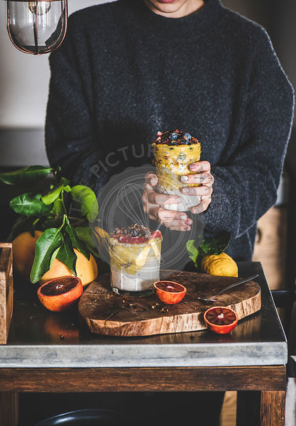 Woman holding glass of muesli with mango smoothie, granola, berries