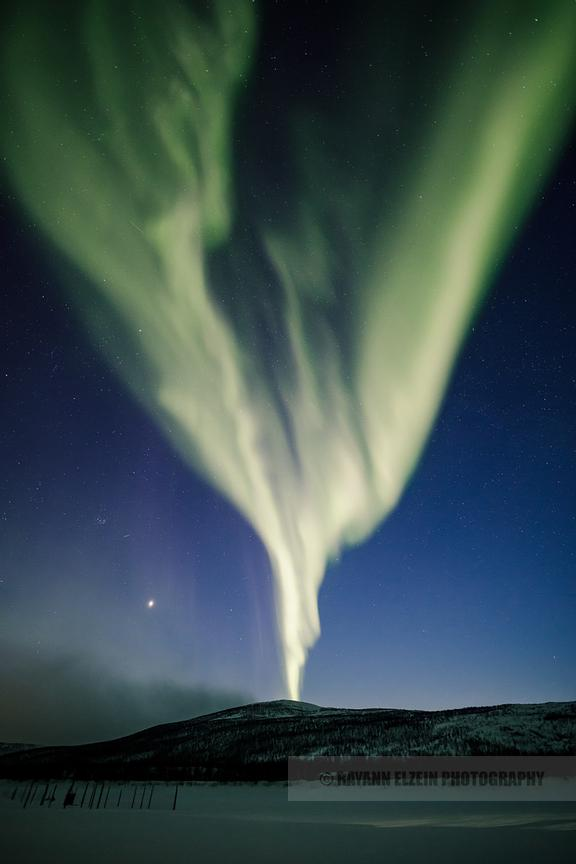 Northern lights shooting straight up from a fell in Lapland