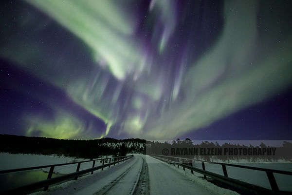 Northern lights filling the sky on top of a bridge in Lapland (Finland)