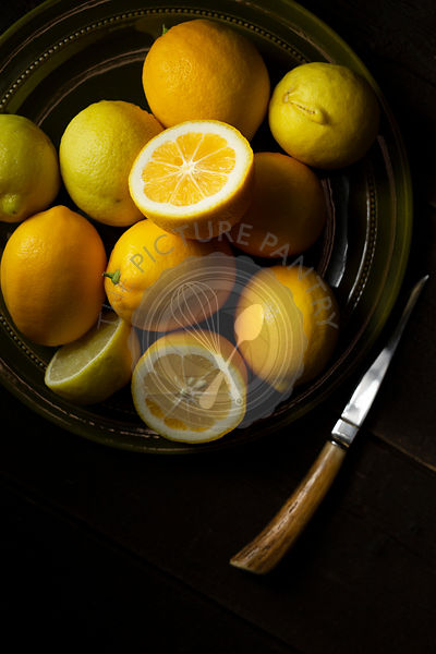Home grown lemons on an olive green plate, with a horn handled k