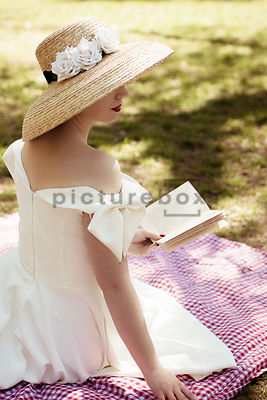 A vintage, mystery woman, reading a book in garden.