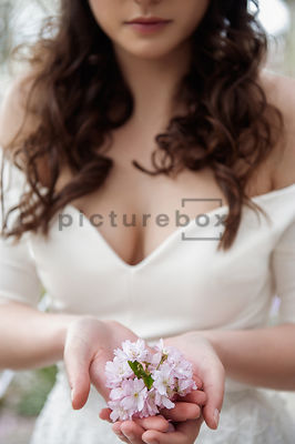 An atmospheric image af a blurred mystery woman in a white dress, in a country garden, holding a flower.