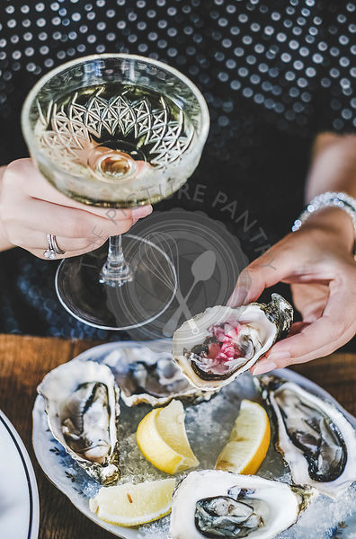 Hands of woman holding glass of champagne and fresh oyster