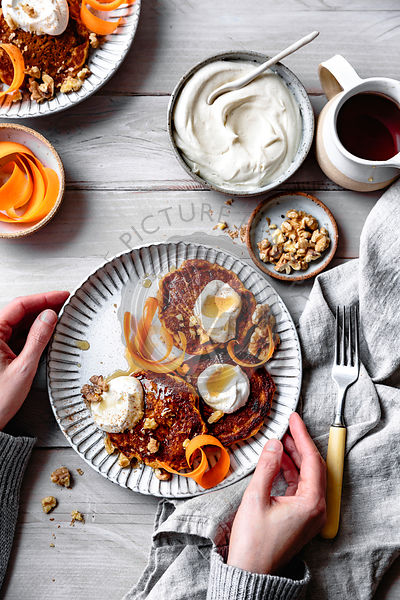 Gluten-free carrot cake pancakes with carrot ribbons, yogurt, maple syrup and walnuts.