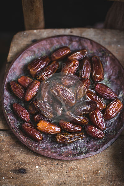 Dried dates on a ceramic plate on a rustic wooden chair