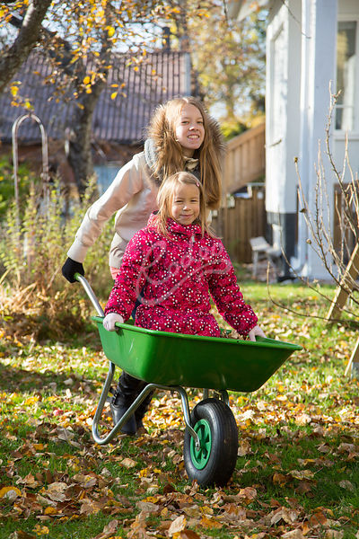 Sisarukset leikkivät kottikärryillä|||Siblings playing with wheelbarrow at garden