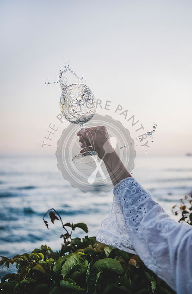 Woman turning glass of white flowing wine with sea background