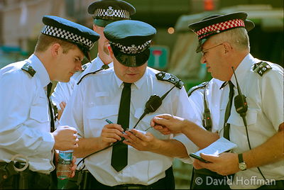 01082202-31A Metropolitan & City of London police at Liverpool Street tube station make notes as demonstrators protest about ...
