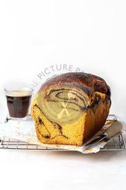 Pumpkin brioche and a cup of coffee on a wire rack
