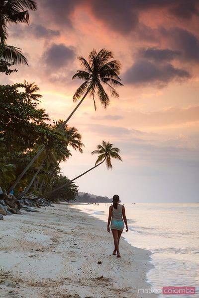 Young woman standing on tropical beach at sunset, Ko Samui