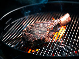Angus beef tomahawk steak being grilled on a BBQ