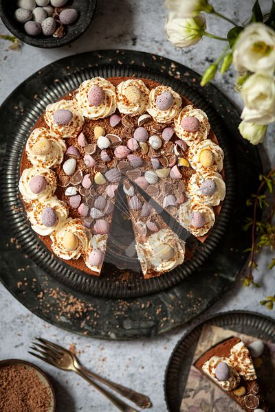 A partially sliced no-bake chocolate cheesecake decorated with whipped cream, chocolate flakes and candy Easter eggs