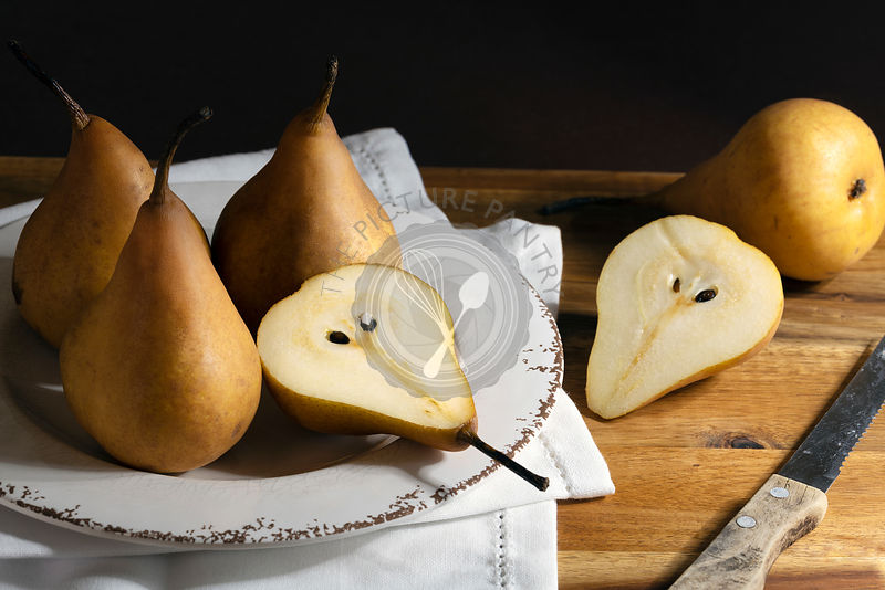 Ripe juicy pears on a rustic wooden table.