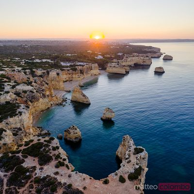 Aerial of the rocky coast at sunrise, Algarve, Portugal