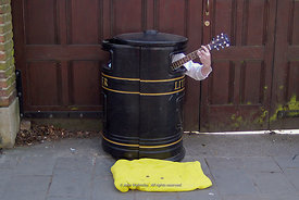 #56472,  Enterprising busker inside a litter bin, Cambridge city centre, UK, 2009.