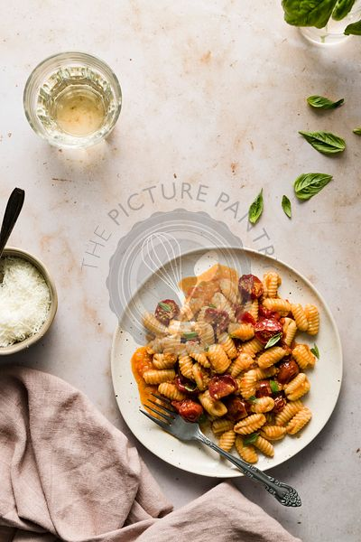 Plate of cavatelli pasta with burst cherry tomatoes, small bowl of parmesan, and glass of wine.