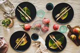 Fall table setting with black dinnerware and cutlery, top view