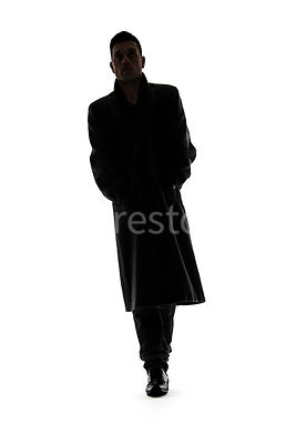 A silhouette image of a mystery man, in a long black winter coat, walking towards camera – shot from low level.