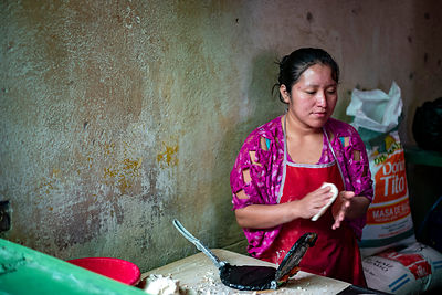 A woman makes tortilla in a shop