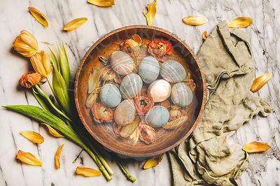 Dyed Easter eggs in wooden plate and blossom flowers