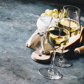 White wine with charcuterie assortment on the stone background