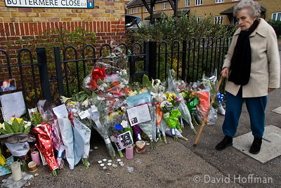 A neighbour looks at memorial flowers left on the estate in Leytonstone where black teenager Paul Erhahon was murdered.