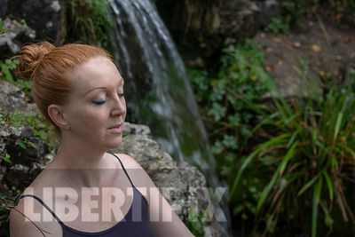ONE LESBIAN MEDITATING NEAR A WATERFALL.