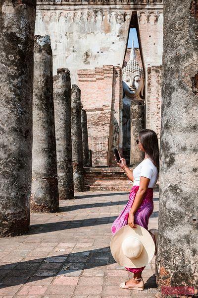 Woman using smartphone in a temple, Sukhothai, Thailand