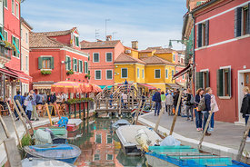 BURANO, ITALY - NOVEMBER 25, 2017: Lots of tourists visiting the beautiful coloured houses in Burano, Venice, Italy.